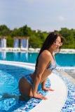 Sexy woman with perfect body shape in fashionable bikini swimwear relaxing at swimming pool edge. Beautiful sexy woman relaxing in Stock Photo