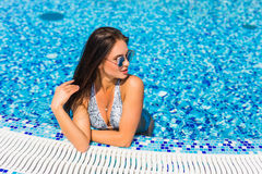 Sexy woman with perfect curvy body shape in fashionable bikini swimwear relaxing at swimming pool edge. Royalty Free Stock Photos