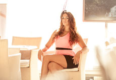 Sexy woman in pink dress sitting on summer terrace Royalty Free Stock Photo