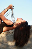 Sexy woman playing with pearl necklace laying on a rock Stock Images