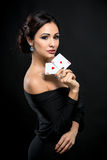 Sexy woman with poker cards. Female player in a beautiful black dress.  two aces Stock Photo