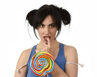 Sexy woman with ponytails biting her lips holding and licking sweet caramel big lollipop Royalty Free Stock Photos
