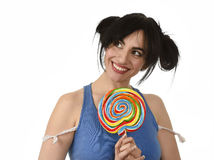Sexy woman with ponytails biting her lips holding and licking sweet caramel big lollipop Stock Images