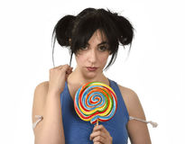 Sexy woman with ponytails biting her lips holding and licking sweet caramel big lollipop Stock Photography