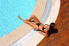 Woman at pool area. Woman sunbathing by a blue swimming pool with a black bikini facing the side. One leg is in the water and the other is on the pool side Royalty Free Stock Photos