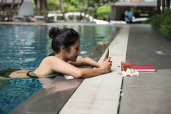 Woman in pool play smartphone. Attractive Asian woman on swimming pool play social media and chat by smartphone. Beautiful Girl relax during summer. Sport and Stock Photos