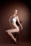 Sexy woman portrait in white bra sit on chair Stock Photos