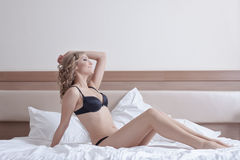 Sexy woman posing in black lingerie on hotel bed Stock Images