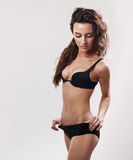 Sexy woman posing in black lingerie. Long curly hair. Sensual look. Fit body Royalty Free Stock Image