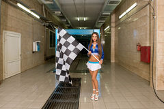 Sexy woman posing with checkered flag at car wash. Sexy brunette posing with checkered flag at car wash Stock Photo
