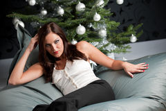 Sexy woman posing in front of Christmas tree Royalty Free Stock Photos