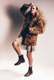Sexy woman posing in fur coat and boots Stock Image