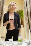 Sexy woman posing with glass of wine in restaurant Stock Image