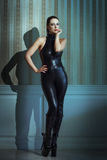 Sexy woman posing in latex catsuit. And high heel boots at vintage wall Royalty Free Stock Photos