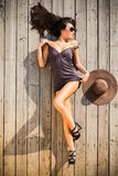 Sexy woman prone on wooden deck Stock Image