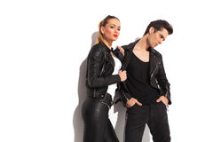 Sexy woman pulling her lover by his leather jacket. Sexy women pulling her lover by his leather jacket and looks to the camera while he looks away Stock Images