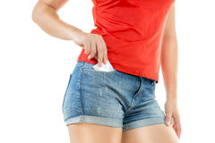 Sexy woman putting condom in jeans shorts pocket Royalty Free Stock Photos