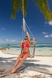 Sexy Woman in Red Bikini on Swing at the Beach Royalty Free Stock Image