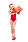 A sexy woman in red Christmas lingerie holding a present Stock Image