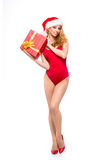 A sexy woman in red Christmas lingerie holding a present Royalty Free Stock Photography