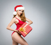 A sexy woman in red Christmas lingerie holding a present Stock Photo