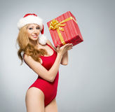 A sexy woman in red Christmas lingerie holding a present Stock Photos