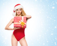 A sexy woman in red Christmas lingerie holding a present Royalty Free Stock Images