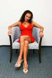 Sexy woman in red dress in chair Royalty Free Stock Images