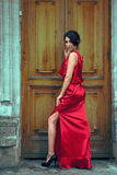 Sexy woman in red dress in front of door Royalty Free Stock Photos