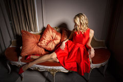 Sexy woman in red dress laying on fancy sofa Stock Photo