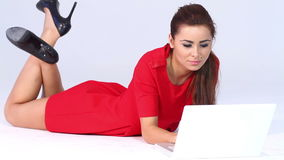 Sexy woman in red dress lying and working stock footage