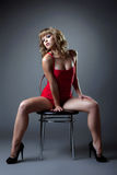 Sexy woman in red dress sit on chair Royalty Free Stock Images