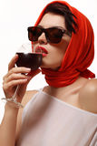 Sexy woman in red drinking wine from a glass Royalty Free Stock Image