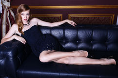 Sexy woman with red hair and freckles posing on black leather divan Royalty Free Stock Images
