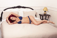 Sexy woman with red hair in lingerie lying on bed Royalty Free Stock Photos