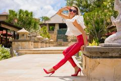 Woman in red leather pants and high heel shoes. Blonde woman in red leather pants and high heel shoes stock photo