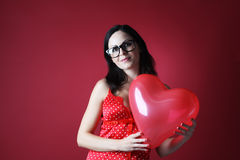 Sexy woman in red lingerie with balloon shape heart on red background Valentines day Stock Photo