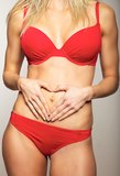 Sexy woman in red underwear. Woman holding hands on her flat stomach making a heart symbol Stock Images
