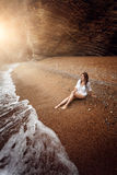 Sexy woman relaxing on deserted beach at sunset Royalty Free Stock Image