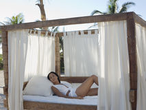 Sexy Woman Relaxing In Four-Poster Bed. Portrait of sexy young woman relaxing in four-poster bed on beach Stock Photography