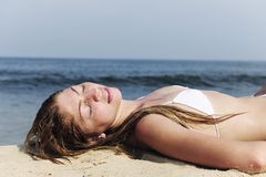 Sexy woman relaxing in the sand near the sea Stock Photo