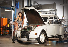 A sexy woman repairing a retro car in a garage Stock Image
