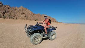 Sexy woman is riding a quad bike in the desert of Egypt. Dynamic view in motion. stock footage