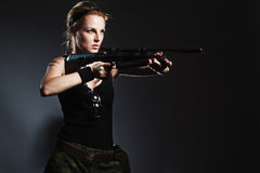 Woman with rifle. On dark stock photo