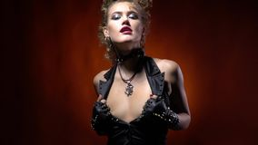Hot rocker woman with blonde hair, pulling on her black vest, slight slow motion. Woman in rocker clothes and crazy hairstyle, turning and pulling on her black stock video