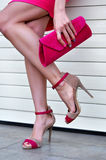 Sexy woman's legs with a fashionable pink high heels and purse. On street Royalty Free Stock Photos