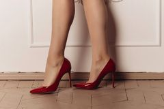 Sexy woman`s legs in red high heels on a parquet floor near a white wall. Sexy woman`s legs in red high heelson a parquet floor near a white wall Stock Images