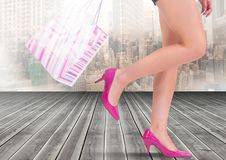 Sexy woman`s legs with shopping bag in front of city. Digital composite of Sexy woman`s legs with shopping bag in front of city Stock Images