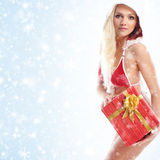 A woman in Santa clothes holding a present Stock Photography