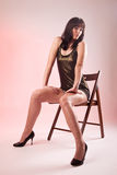 Sexy woman seated on wooden chair Royalty Free Stock Images